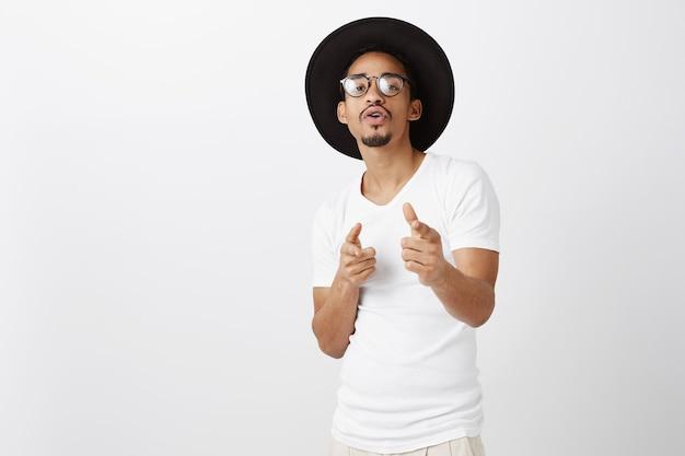 Sassy knappe hipster afro-amerikaanse man in glazen en hoed wijzende vingers, gefeliciteerd, goed gedaan gebaar