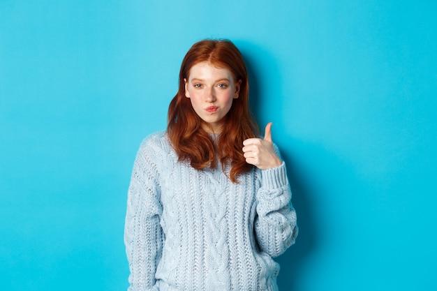Sassy roodharig meisje in trui, ziet er tevreden uit en toont duim, leuk en akkoord, staande over blauwe achtergrond.
