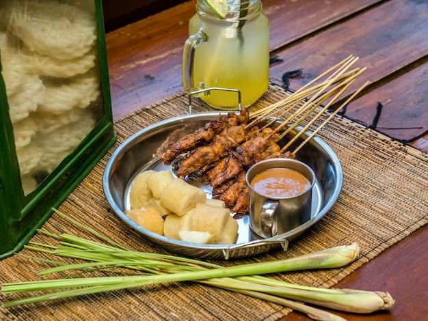Satay indonesische gerechten geserveerd met pindasaus en rijstcake