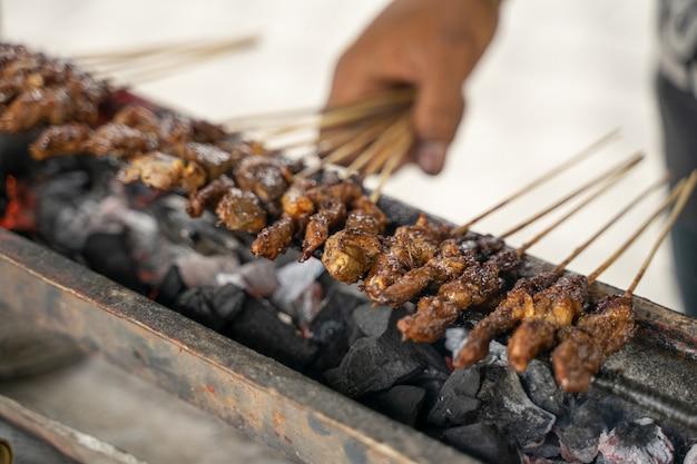 Saté ayam traditioneel culinair van saté spies met kip wordt gegrild met houtskool