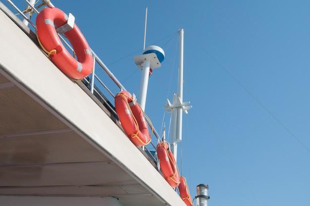 Satellietantenne en reddingsboeiringen op het scheepsdek