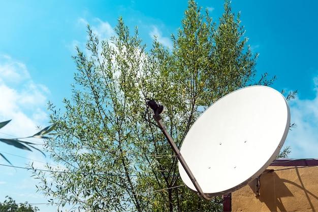 Satellietschotel aan de muur van een landhuis