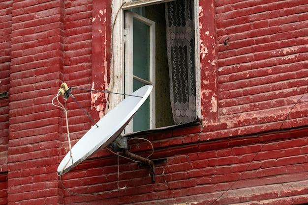 Satellietschotel op de muur van een oud bakstenen huis