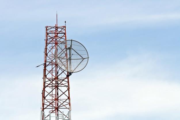 Satellietschotel op telecommunicatie radioantenne toren met blauwe hemel