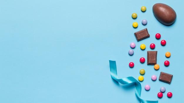 Satijnen lint; edelstenen snoep en paaseieren met ruimte voor het schrijven van de tekst op blauwe achtergrond