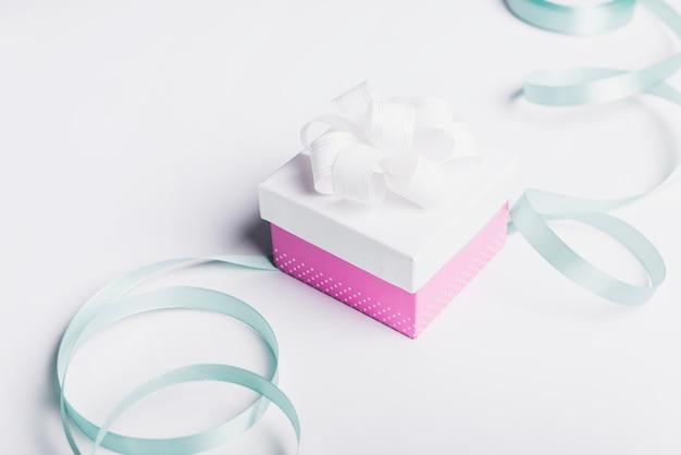 Satijnen lint met gesloten geschenkdoos op witte achtergrond