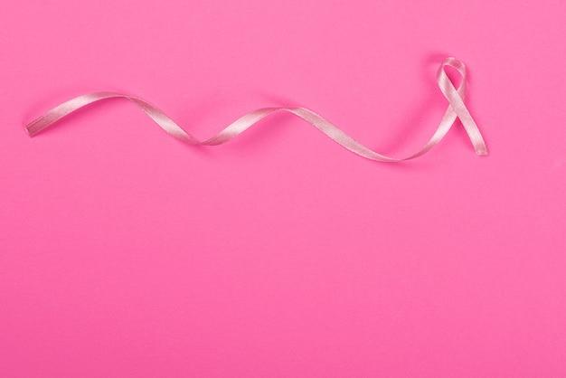 Satijnen lint teken op de roze achtergrond en het concept van borstkanker