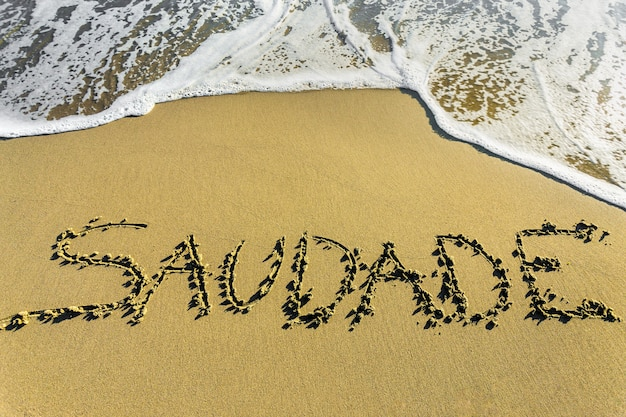 Saudade. het beroemde portugese woord dat een vorm van weemoedig schrijven op het zand beschrijft