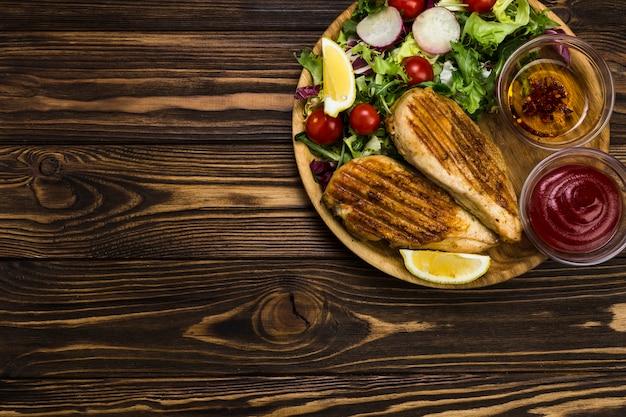 Saus en specerijen in de buurt van salade en kip