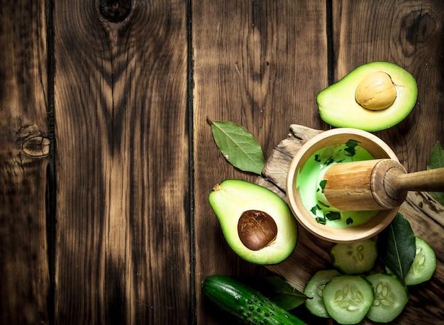 Saus in een vijzel met stamper, avocado en komkommer. op houten achtergrond.