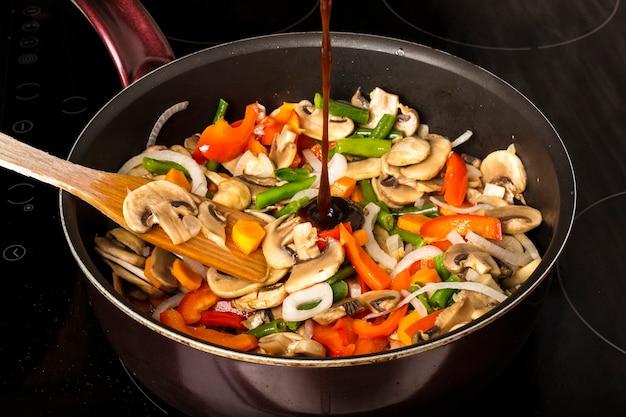 Saus toevoegen aan gebakken groenten met champignons in een koekenpan op een donkere achtergrond