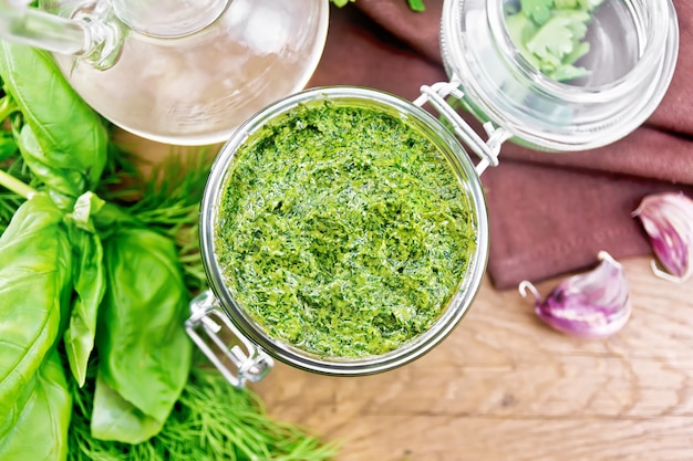 Saus van dille, peterselie, basilicum, koriander, andere pittige kruiden, knoflook en plantaardige olie in een glazen pot, servet op houten plank achtergrond van bovenaf