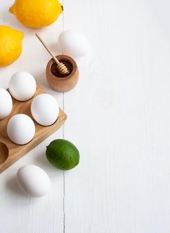 Sausbereiding: honing, eieren, citroen en limoen. producten liggen op witte houten achtergrond.