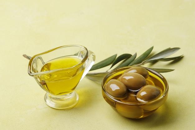 Sauskom met olijfolie, groene olijven en bladeren op een groene achtergrond, bovenaanzicht