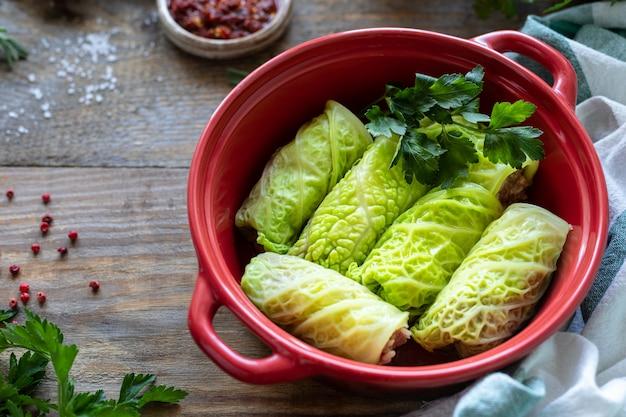 Savooiekoolbroodjes die met vlees, rijst en groenten op een rustieke lijst worden gevuld