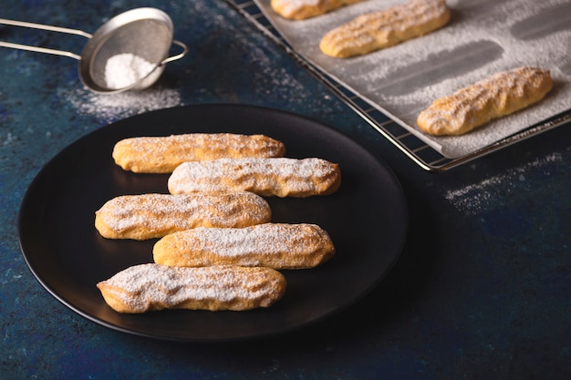 Savoyardi koekjes bestrooid met poedersuiker op blauw