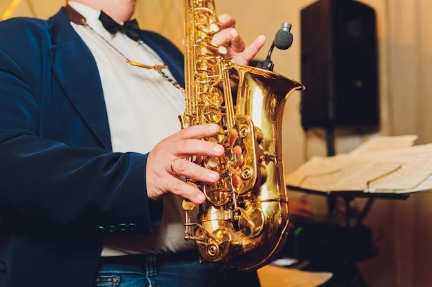 Saxofoon klassieke muziek instrument saxofonist met altsax close-up op zwart.