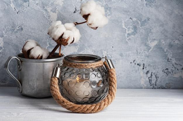 Scandinavisch interieur met katoenen bloemen en aangestoken kaarsen