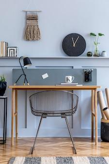 Scandinavisch interieur van open ruimte met houten bureau, moderne stoel, houten lambrisering met plank, plant, tapijt, kantoorbenodigdheden en elegante persoonlijke accessoires in woondecoratie.
