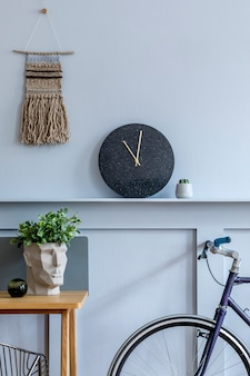 Scandinavisch interieur van thuiskantoorruimte met houten bureau, moderne stoel, houten lambrisering met plank, plant, tapijt, fiets, kantoorbenodigdheden en elegante persoonlijke accessoires.