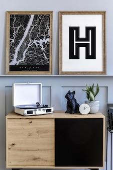 Scandinavisch interieur van woonkamer met twee posterframes, houten commode, klok, planten en decoratie, tapijt
