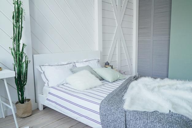 Scandinavisch modern, gezellig eco-interieur, witte tafel en spiegel in slaapkamer