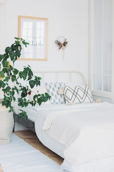 Scandinavisch modern, knus eco-wit interieur in slaapkamer, grote kasplant, minimalisme