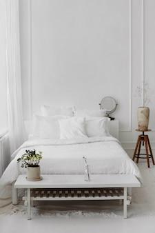 Scandinavisch slaapkamerinterieur van rieten fauteuilbed en kleine houten tafel met houten vaas