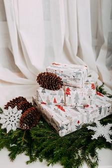 Scandinavische kerstkaart met geschenken in witte dozen.