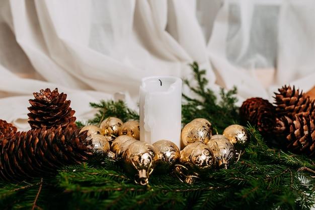 Scandinavische kerstkaart met witte stof en kerstkrans met witte kaarsen erin