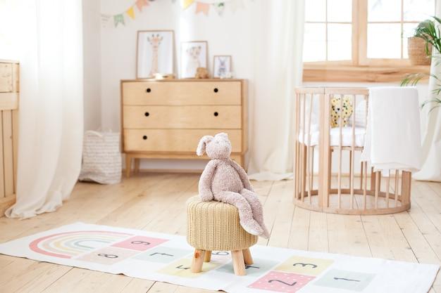 Scandinavische kinderkamer: een mand voor speelgoed, een pluche konijn dat op een stoel zit, een wieg voor een babybed. modern interieur van een kinderkamer. rustiek. kopieer ruimte. hygge. kleuterschool interieur