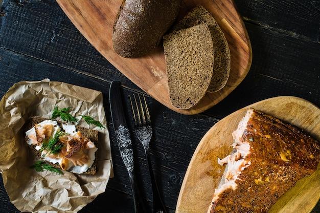 Scandinavische sandwich met gerookte zalmfilet op zwart brood met zachte kaas