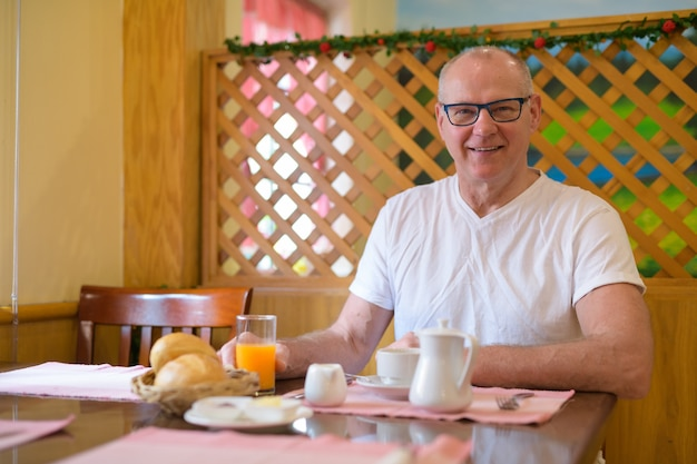 Scandinavische senior man zit in restaurant klaar voor het ontbijt