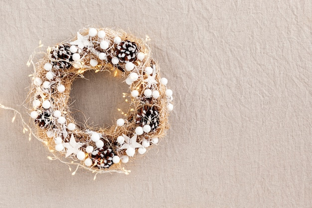 Scandinavische stijl, handgemaakte, milieuvriendelijke, stro kerstkrans met dennenappels en kerstverlichting, bovenaanzicht