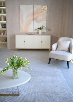 Scandinavische stijl lichte klassieke moderne luxe witte woonkamer met marmeren tafel, nieuwe stijlvolle meubels, ladekast, gezellige fauteuils, kamerplanten. minimalistisch scandinavisch interieurontwerp