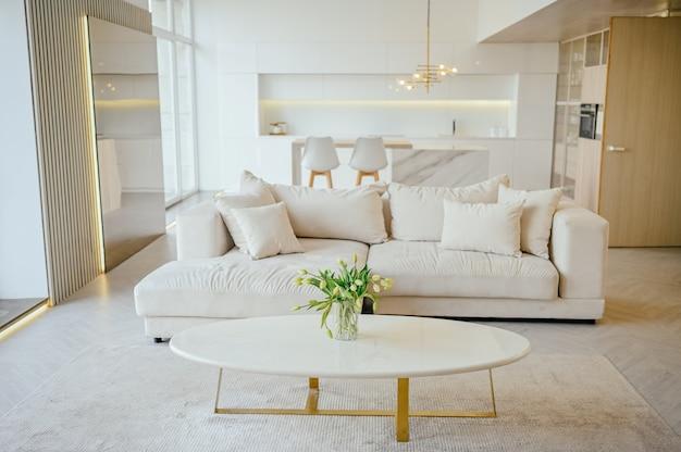 Scandinavische stijl lichte klassieke moderne luxe woon-eetkamer en keuken met houten, witte, marmeren details, nieuwe stijlvolle meubels, gezellige slaapbank, minimalistisch scandinavisch interieurontwerp.