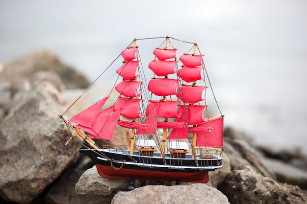 Scarlet sails. een eenzaam schip tegen de ochtendhemel. schip in het water. alexander green. fotografie voor de roman van alexander green. schip met dieprode zeilen in de rivier