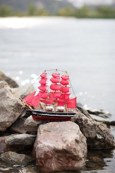 Scarlet sails. een eenzaam schip tegen ochtendhemel. schip in water. alexander green. fotografie voor de roman van alexander green. schip met dieprode zeilen in de rivier. houten beeldje van een schip met rode zeilen