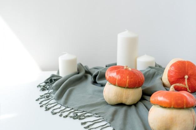 Scène met wollen deken, kaarsen en pompoenen.