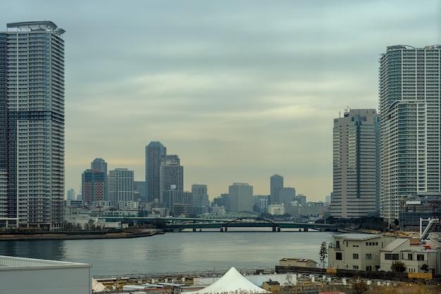 Scène van de bouw van cityscape met brug in schemeringtijd rond odaiba-gebied, tokyo, japan