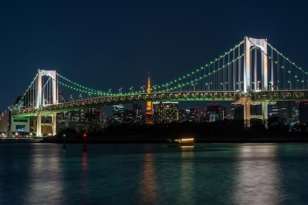 Scène van de regenboogbrug van tokyo die de toren van tokyo in de schemeringtijd, odaiba, japan kan zien