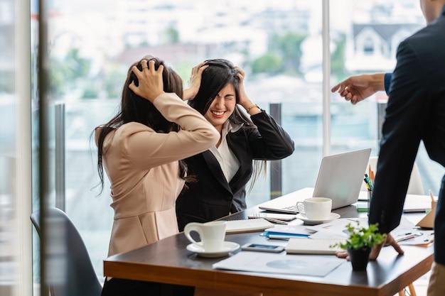 Scène van furious baas schelden aziatische jonge paar zakenvrouw in formele pak punt