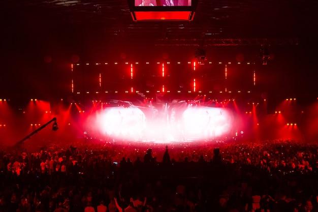 Scène verlicht door prachtige stralen van verlichtingsapparatuur. het concertpubliek vermaakt zich in het midden van de grote zaal. televisie wordt live uitgezonden. veel mensen kijken naar het podium.