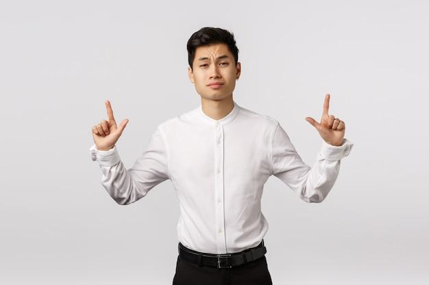 Sceptisch aantrekkelijke aziatische zakenman hebben twijfels, omhoog fronsen met ongeloof of aarzeling, grijns veroordelend en minachting, geloof niet dat dit product zijn aandacht waard is
