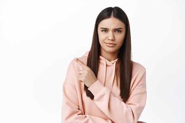 Sceptisch brunette meisje, wijzende vinger naar het logo in de linkerbovenhoek, twijfels hebben, fronsen en onzeker naar voren staren, staande tegen een witte muur