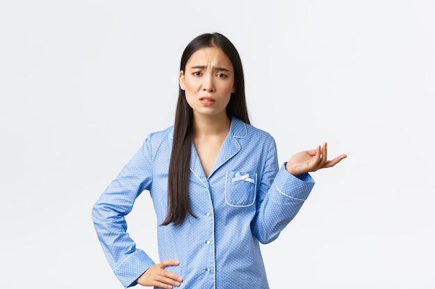 Sceptisch en gefrustreerd aziatisch meisje in blauwe pyjama dat klaagt, ergens ruzie over maakt, fronsend en verbaasd de hand opsteekt, niet begrijpt wat er gebeurt, verward kijkt.
