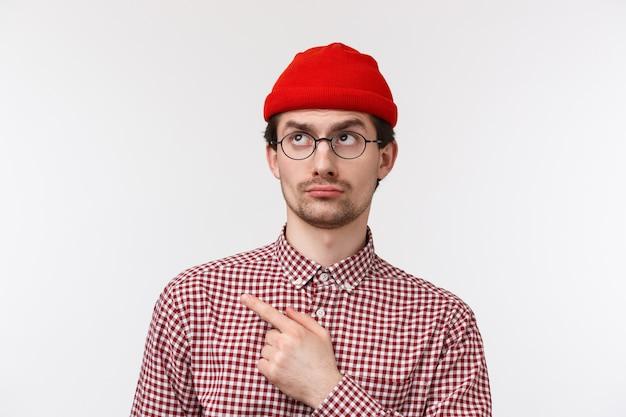 Sceptisch en niet onder de indruk knappe jonge hipster-man ziet er veroordelend en ontevreden uit, wijzend starend in de linkerbovenhoek teleurgesteld, terughoudend