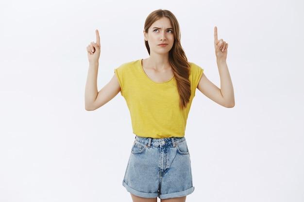 Sceptisch en ontevreden jong meisje klagen, vingers omhoog wijzend naar advertentie