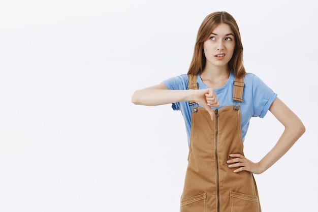 Sceptisch en teleurgesteld meisje toont duim omlaag en kijkt linksboven naar banner of logo
