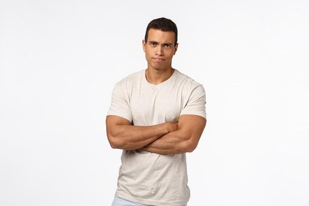 Sceptisch en veroordelend serieus ogende knappe sterke man met enorme biceps